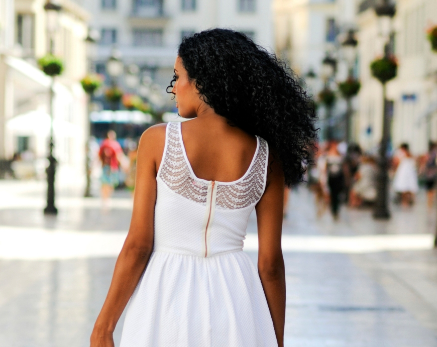 Black woman, afro hairstyle, walking barefoot on a commercial street